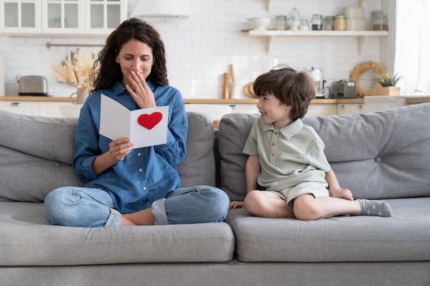La mamma positiva legge i saluti dal biglietto fatto dal figlio del bambino in età prescolare alla festa della mamma o all'evento di compleanno birthday