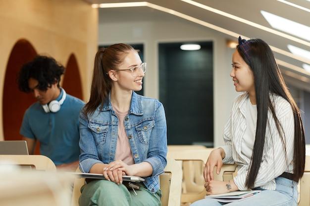 Ragazze multietniche positive in abiti casual seduti sulle sedie in auditorium e chiacchierando durante la pausa all'università