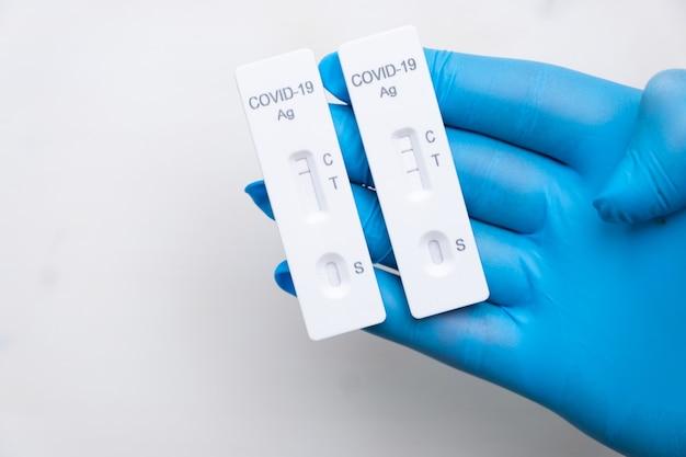 Test antigenico covid positivo e negativo per il rilevamento rapido della malattia nella mano dei medici