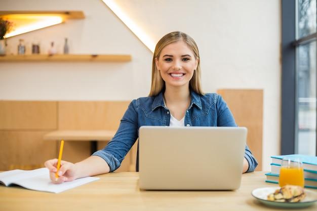 Positiva bella donna attraente seduta davanti al computer portatile e prendere appunti mentre si lavora in ufficio