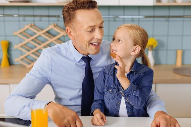 Positiva bella ragazza bionda seduta sulle ginocchia di suo padre e dandogli un biscotto divertendosi insieme