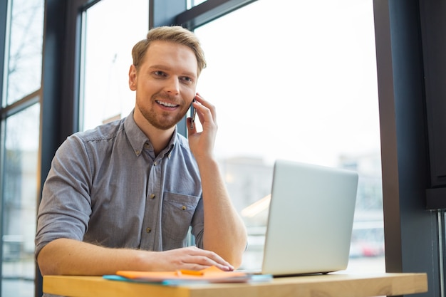 Uomo bello bello positivo che tiene il suo smartphone e che effettua una chiamata mentre era seduto al tavolo del caffè