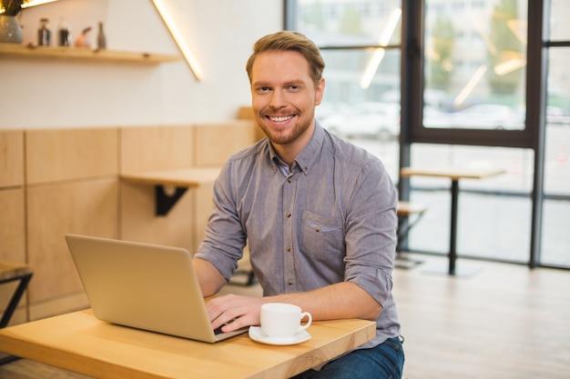 Positivo bel uomo felice seduto al computer portatile e sorridente mentre beve un caffè nella caffetteria