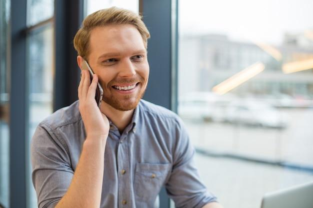 Positivo bello gioioso uomo sorridente e avere una piacevole conversazione telefonica mentre si è nella caffetteria