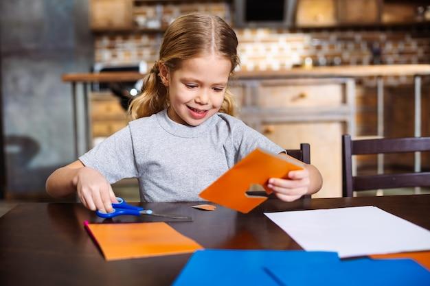 Bambina piacevole positiva che si siede al tavolo mentre si effettua una carta festiva