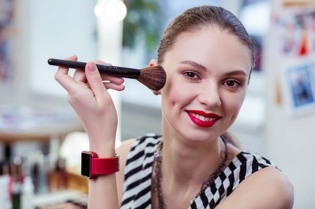 Bella donna positiva che sorride mentre usa il pennello per il trucco mentre applica la polvere