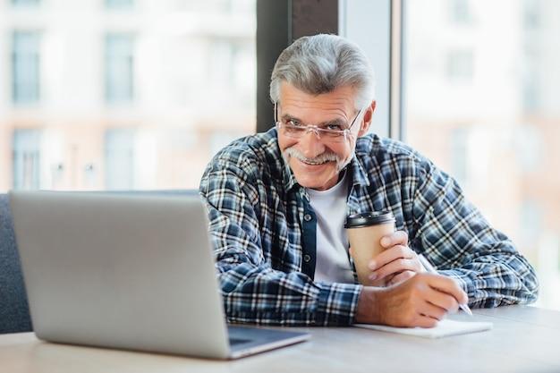 Vecchio uomo d'affari positivo che lavora al computer portatile in caffè che beve caffè