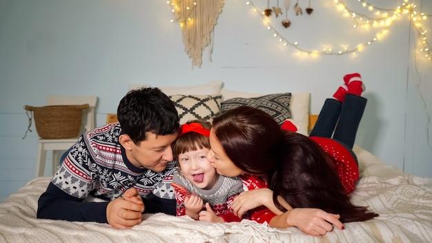 Genitori positivi giacciono su un letto accogliente e baciano la figlia carina con una caramella in posa al primo piano di natale della famiglia