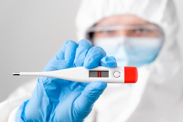 Test di gravidanza positivo nella mano dei medici in tuta protettiva dpi, guanti di gomma, maschera facciale, sicurezza