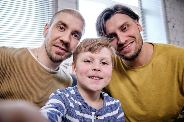 Ragazzo preadolescente positivo che si fa selfie con i suoi due padri sorridenti per postare sui social media