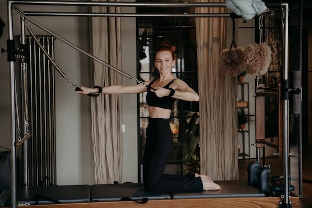 Positiva donna dai capelli rossi in forma istruttore di pilates facendo esercizi di forza del braccio sopra il riformatore cadillac sorridendo felicemente durante l'allenamento in palestra o in studio, utilizzando attrezzature per il fitness speciali
