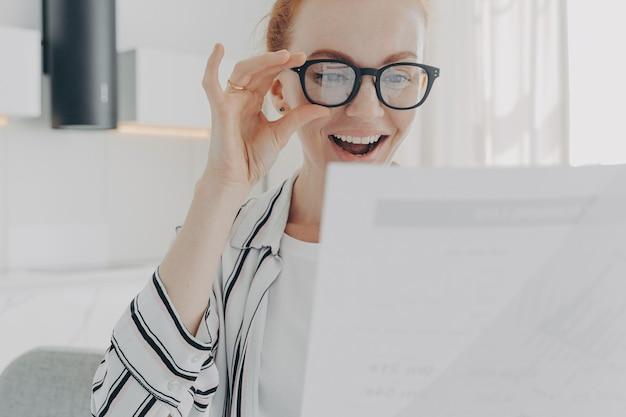 La giovane donna rossa positiva sorride ampiamente indossa occhiali trasparenti concentrati sui documenti
