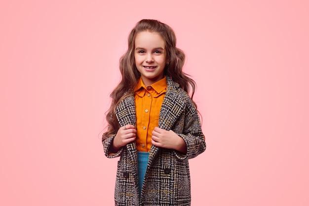 Studentessa positiva in abiti casual e caldo cappotto a scacchi sorridendo e guardando la fotocamera mentre rappresenta la moda per bambini su sfondo rosa