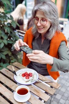 Una donna anziana positiva scatta una foto di un delizioso dessert alla fragola sulla terrazza del caffè all'aperto