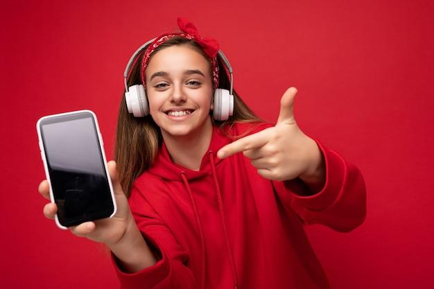 Positivo, sorridente, carino, bruna, ragazza, il portare, felpa rossa, isolato, su, sfondo rosso, presa a terra