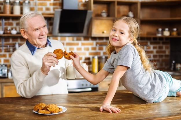 Bambina sorridente positiva che mangia i biscotti con suo nonno mentre riposa in cucina