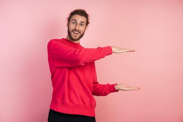 Uomo positivo e sorridente che mostra con le mani