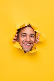 Giovane maschio barbuto sorridente positivo che guarda l'obbiettivo attraverso il foro in carta gialla strappata