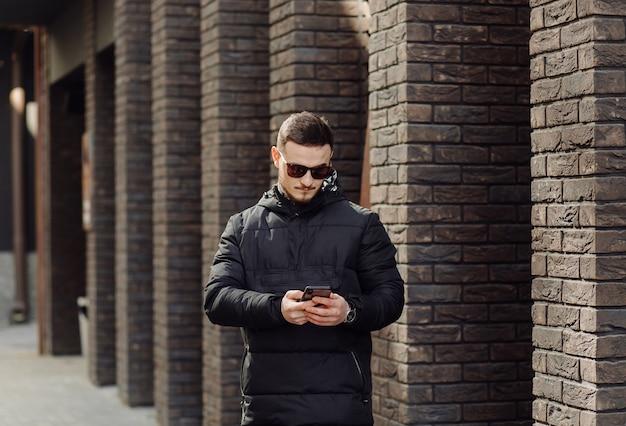 Giovane maschio sorridente positivo in vestiti alla moda in piedi fuori da solo vicino al muro di edificio urbano e parlando al telefono cellulare