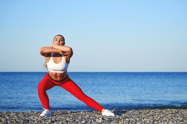 Donna sportiva positiva su una formazione mattutina estiva sulla spiaggia in leggings rossi, allenamento sullo sfondo della costa del mare, ragazza atleta accovacciata