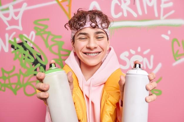 L'adolescente positivo sorride a trentadue denti indossa le parentesi graffe sui denti chiude gli occhi vestito con una felpa con cappuccio tiene due bottiglie spray disegna graffiti in luogo pubblico ha un aspetto fresco gode del tempo libero