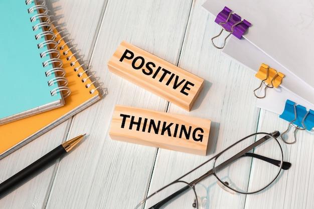 Parole di pensiero positivo scritte su blocchi di legno vicino a forniture per ufficio