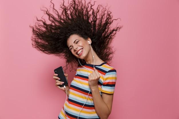 Donna positiva 20s con capelli tremanti che canta mentre tiene in mano lo smartphone e ascolta la musica tramite le cuffie isolate sul rosa