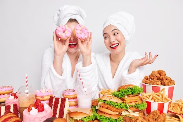 La donna positiva si diverte a casa copre gli occhi con due ciambelle mangia cibo spazzatura insieme al migliore amico.