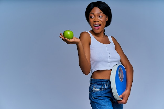 La donna positiva tiene le scaglie viola nella sua mano e una mela verde sul palmo teso. concetto di dieta