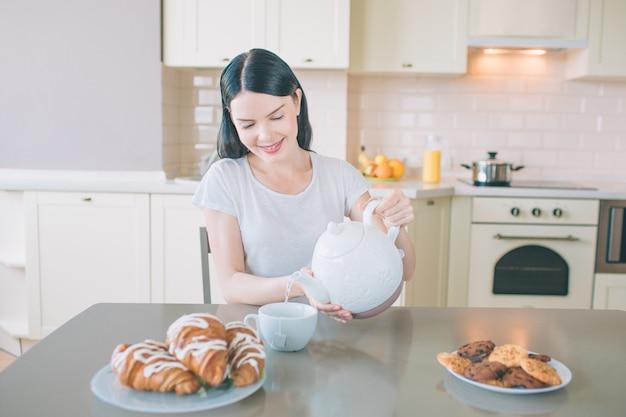 La donna positiva si siede al tavolo in cucina. lei sorride e versa acqua nella tazza bianca.