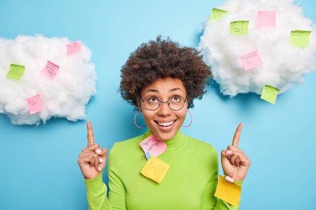 La donna positiva sorride a trentadue denti e punti sopra l'essere di buon umore circondato da note appiccicose colorate fa la lista da fare per la settimana indossa gli occhiali dolcevita verde isolato sulla parete blu