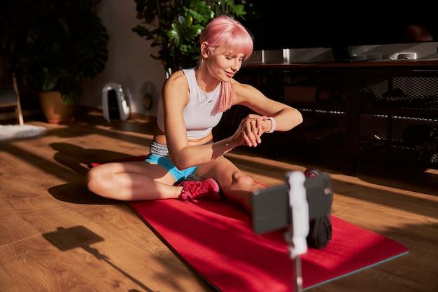 Donna positiva in elegante tuta da ginnastica controlla il polso su smartwatch a casa allenamento