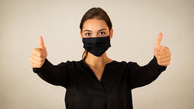 Donna positiva che indossa la maschera facciale nera che mostra i suoi pollici in su