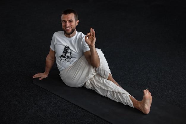 Istruttore di yoga positivo che fa stretching e mostra bene. l'uomo si dedica allo sport in uno studio fitness.