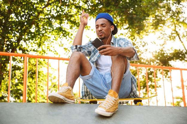 Positivo giovane uomo africano in auricolari