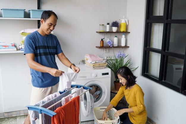 Giovani coniugi asiatici positivi che fanno il bucato regolare e che sorridono insieme a casa