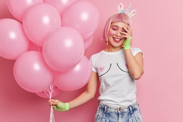 La giovane donna asiatica positiva con i capelli rosei tiene la mano sul viso sorride allegramente vestita in abiti casual tiene un mazzo di palloncini che si trova alla festa delle galline