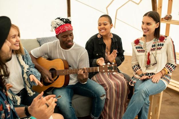 Positivo giovane musicista nero suonare la chitarra e cantare canzoni con gli amici in tenda