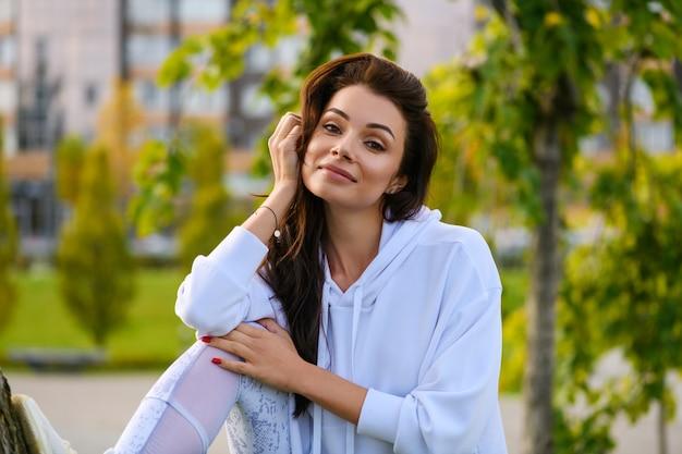 Positiva giovane donna bruna sullo sfondo del parco cittadino verde dopo lo stretching, fitness in felpa con cappuccio bianca e leggings