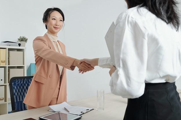 Giovani donne d'affari positive che si stringono la mano dopo aver discusso di questioni importanti alla riunione