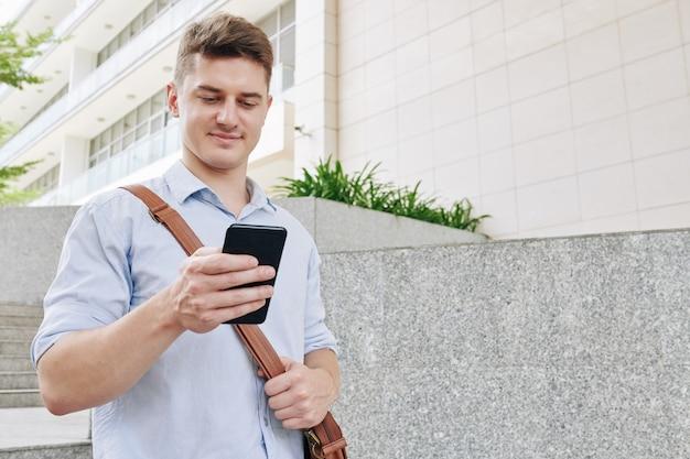 Positivo giovane imprenditore camminare all'aperto e controllare i messaggi di testo nello smartphone