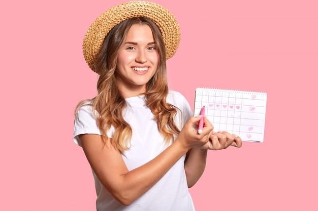 La giovane donna europea positiva in cappello di paglia, maglietta bianca casuale, usa l'indicatore per dimostrare il periodo mestruale sul calendario, posa contro la parete rosa. assistenza sanitaria delle donne e concetto di pms