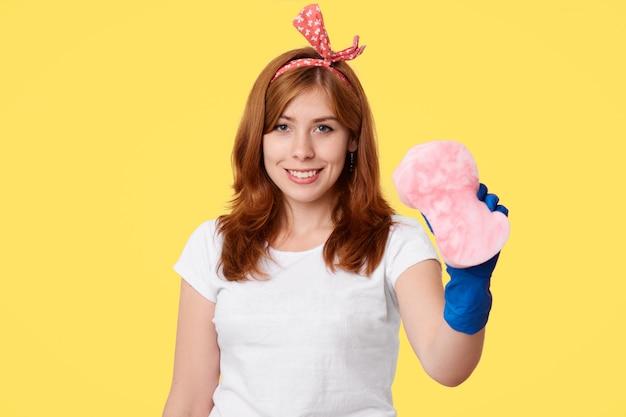 La giovane femmina positiva fa la pulizia della tuta nel suo appartamento, gode del processo, indossa guanti di gomma blu, tiene la spugna, isolata sopra la parete gialla. casalinga con mop. concetto di pulizia