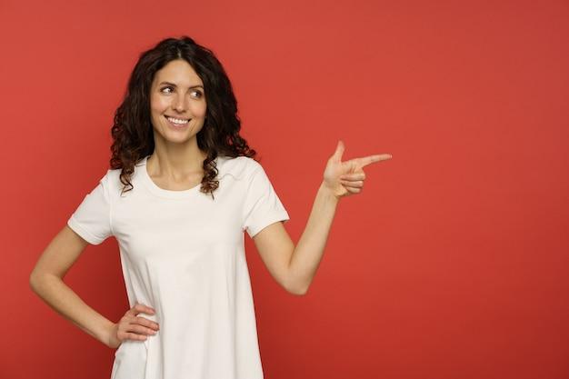 La ragazza positiva con l'acconciatura riccia punta da parte con un sorriso curioso e felice che incoraggia sorpreso. ritratto di donna casual in bianco oversize t-short display company, business o pubblicità di servizio