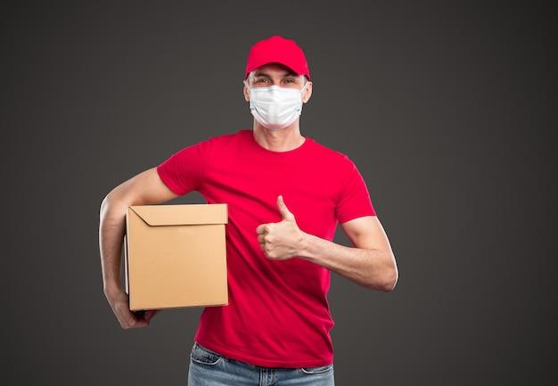 Corriere maschio giovane positivo in berretto rosso e maglietta con maschera protettiva sul viso che tiene la scatola del mestiere e mostra il gesto del pollice in su, mentre si trova in piedi su sfondo grigio