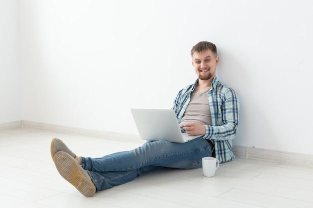 Giovane positivo in abiti casual e occhiali che naviga in internet utilizzando il wi-fi e un laptop in cerca di alloggi in affitto. concetto di inaugurazione della casa e di ricerca di appartamenti, spazio di copia