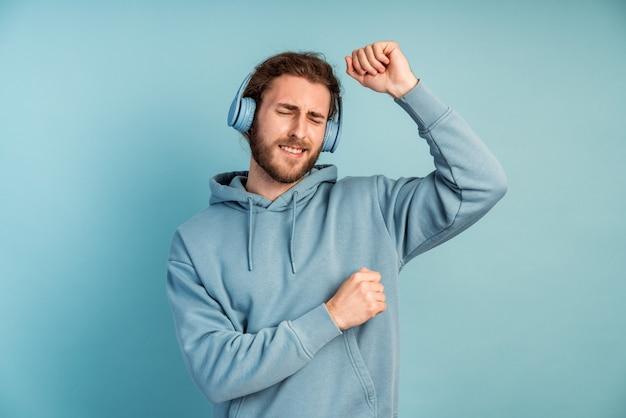 Giovane positivo in cuffie divertendosi. un uomo barbuto balla mentre ascolta la musica