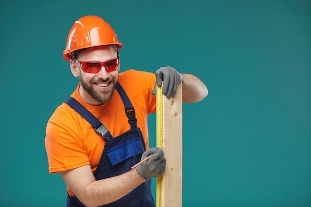 Giovane positivo che dimensiona plancia di legno