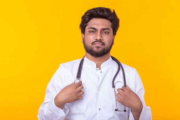Positivo giovane medico di razza mista in camice bianco con uno stetoscopio in posa su una parete gialla. concetto di medicina efficace e consiglio del medico.