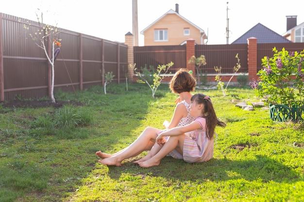 La giovane madre positiva, la figlia e il cane sono sdraiati sul prato della loro casa di campagna. e godersi un riposo congiunto durante il fine settimana nella stagione calda.